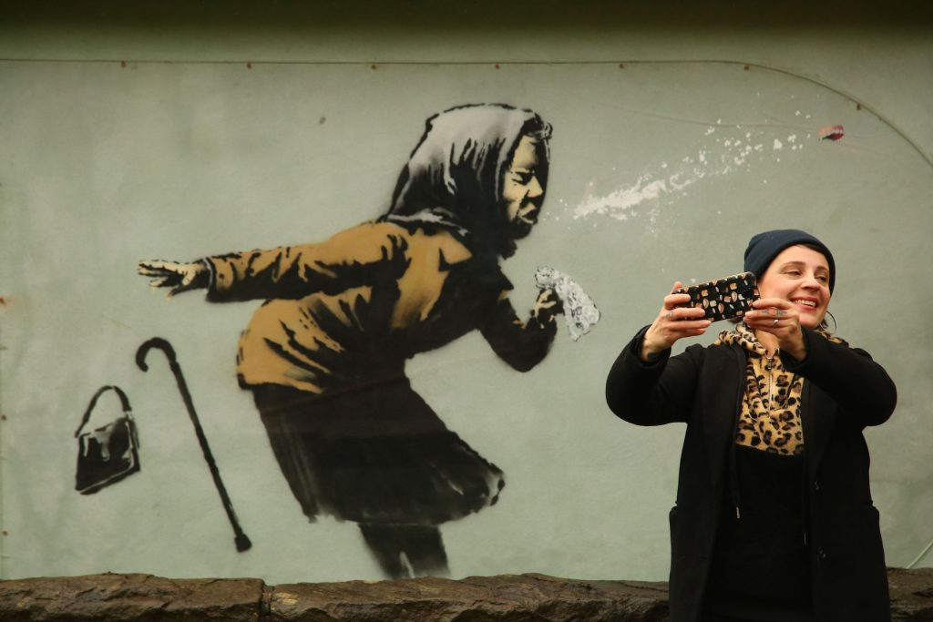 "A person photographs a mural created by British artist Banksy entitled ""Aachoo!!"" showing a woman wearing a headscarf sneezing and dropping their handbag and cane, in Bristol. (Photo by Geoff Caddick/AFP via Getty Images.)"