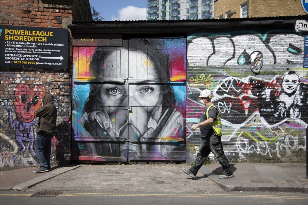 Virus face mask street art and graffiti on Brick Lane in Shoreditch as lockdown continues and people observe the stay at home message in the capital on May 12, 2020, in London. Photo by Mike Kemp/In PIctures via Getty Images.