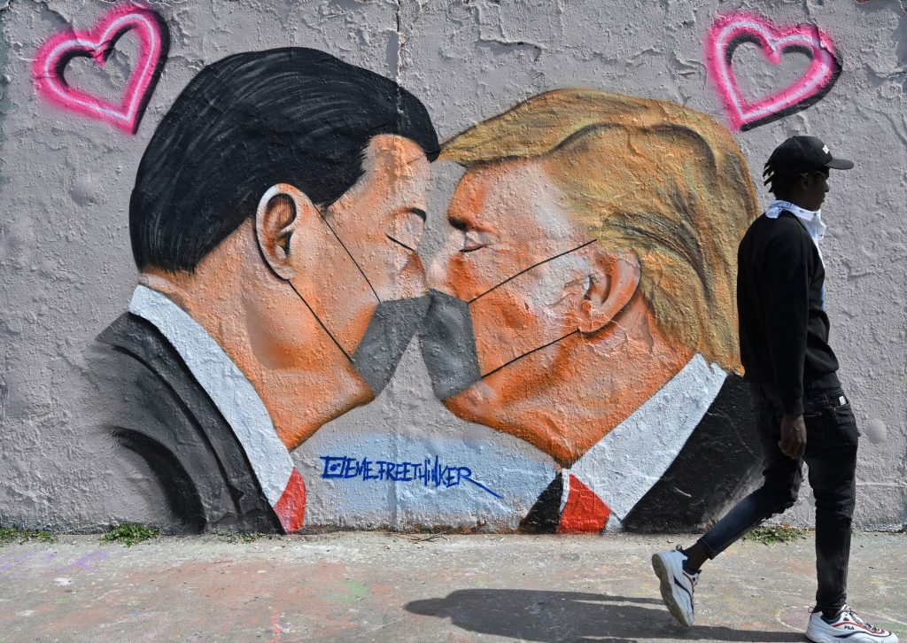 A mural painting by graffiti artist Eme Freethinker features likenesses of US President Donald Trump and Chinese premier Xi Jinping wearing face covers, in Berlin on April 28, 2020. Photo by John MacDougall/AFP via Getty Images.