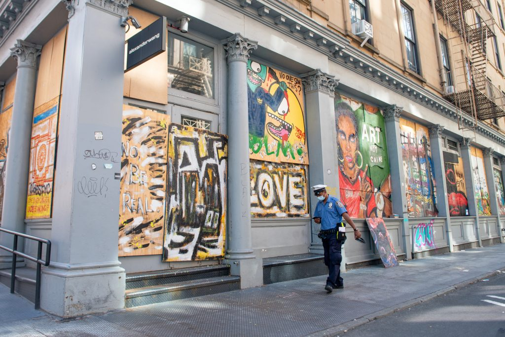 An NYPD traffic officer walks past street art in SoHo as the city continues Phase 4 of re-opening following restrictions imposed to slow the spread of coronavirus on August 20, 2020 in New York City. Photo by Alexi Rosenfeld/Getty Images.