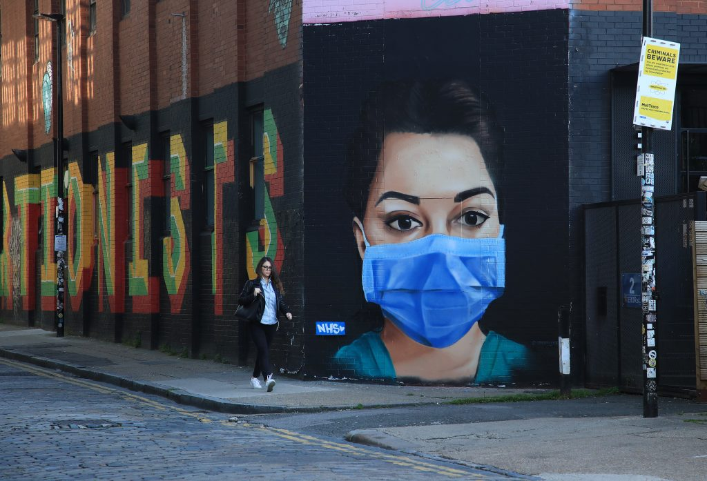 A woman walks past a piece of street art depicting an NHS worker on April 21, 2020 in the Shoreditch area of London, England. Photo by Andrew Redington/Getty Images.