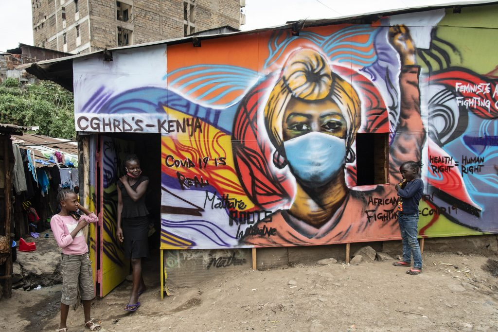 A girl walks out of a building decorated with educational graffiti about safety measures and COVID-19 on July 6, 2020 in Nairobi, Kenya. Photo by Alissa Everett/Getty Images.