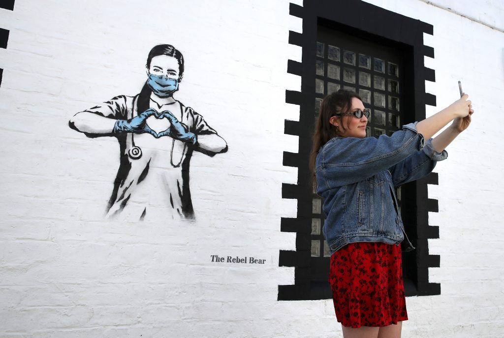 Hannah McGee takes a selfie beside a piece of art by the artist Rebel Bear after it appeared on a wall on Ashton Lane in Glasgow. Photo by Andrew Milligan/PA Images via Getty Images.