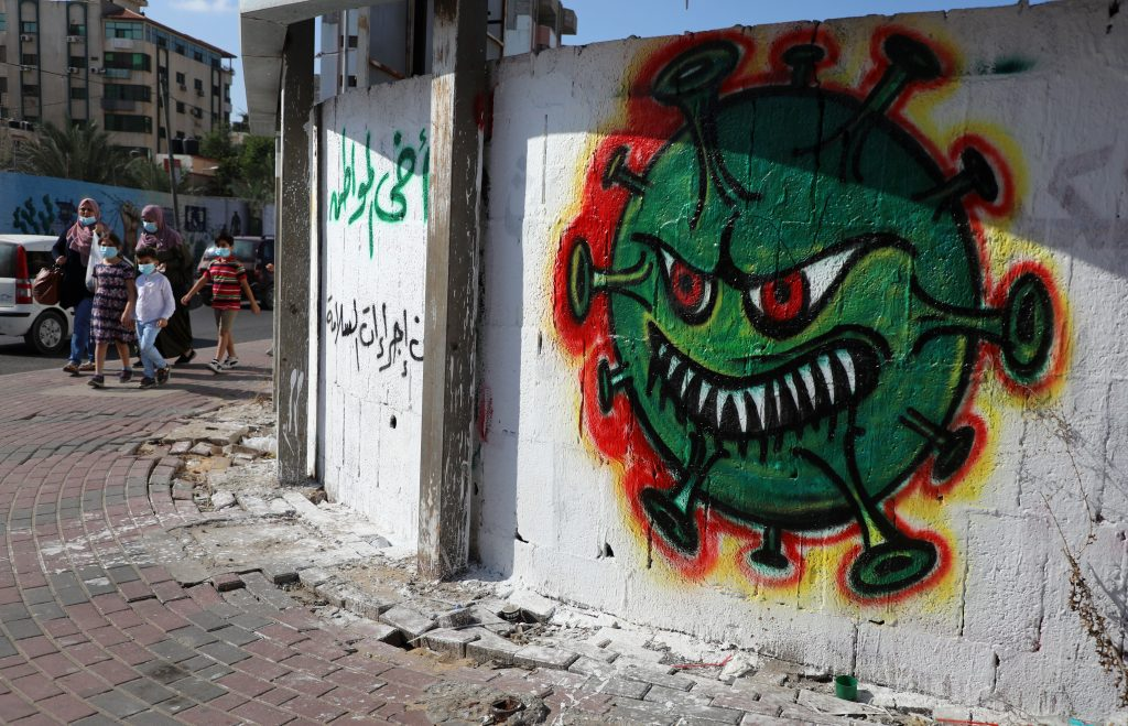 Palestinians, wearing protective face masks,walk past street art showing a COVID-19 virus, in Gaza city on October 5, 2020. Photo by Majdi Fathi/NurPhoto via Getty Images.