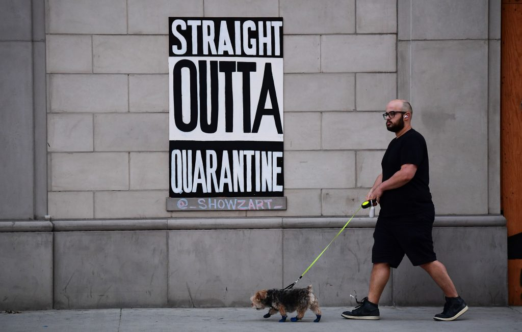 A man walks his dogs past a public art installation aimed at turning boarded up shopfronts into works of art in Los Angeles, California on April 28, 2020. The initiative was launched by street artist Jeremy Novy and Art Share LA, including work seen here by @_ShowzArt_. Photo by Frederic J. Brown/AFP, via Getty Images.