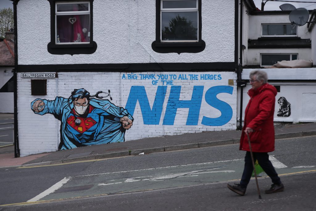 A woman walks past street art supporting the NHS, near to the Ulster Hospital in Dundonald, Belfast. Photo by Niall Carson/PA Images via Getty Images.