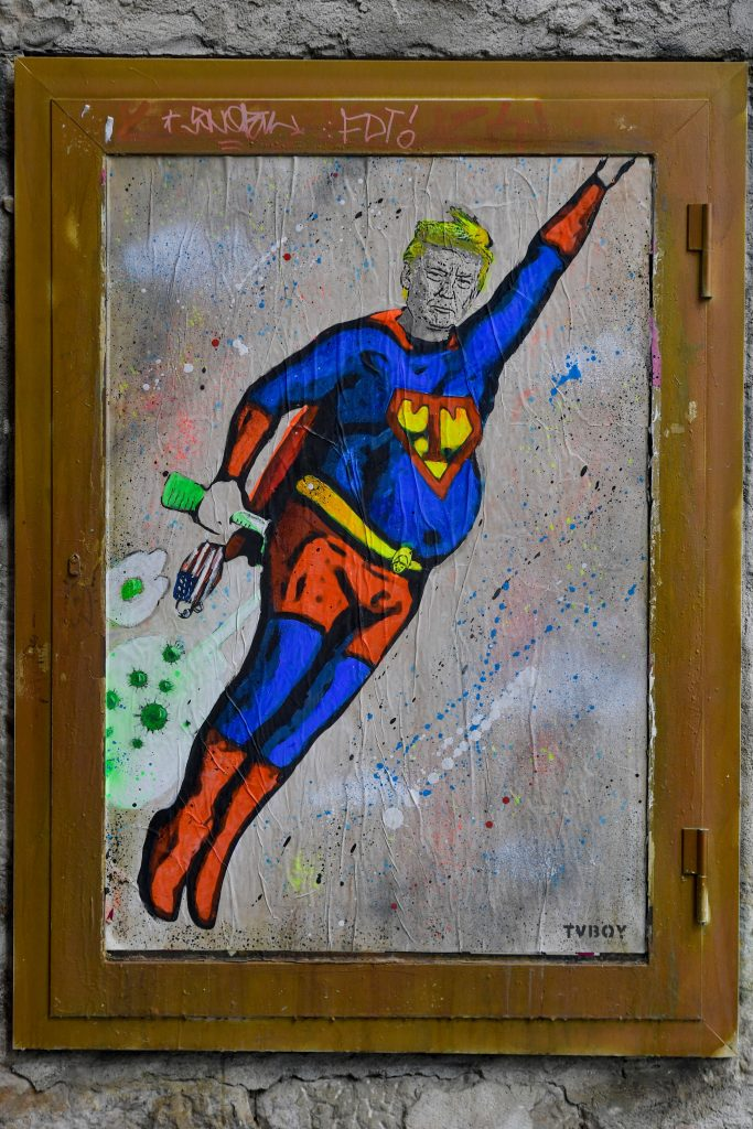 A new artwork by street artist TVBoy depicting US President Donald Trump dressed up in a Superman costume and flying through COVID-19 clouds is pictured in a street in Barcelona on October 8, 2020. Photo by Pau Barrena/AFP via Getty Images.