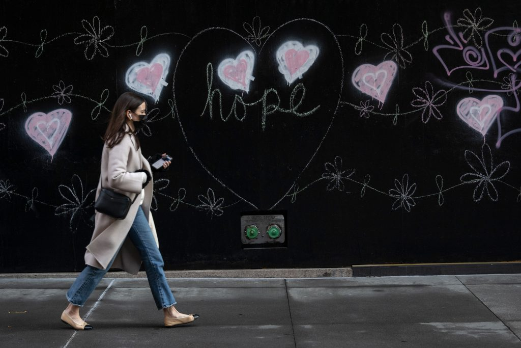 "A woman wearing a mask walks past street art of hearts that reads, ""Hope"" on December 10, 2020 in New York City. Photo by Alexi Rosenfeld/Getty Images."
