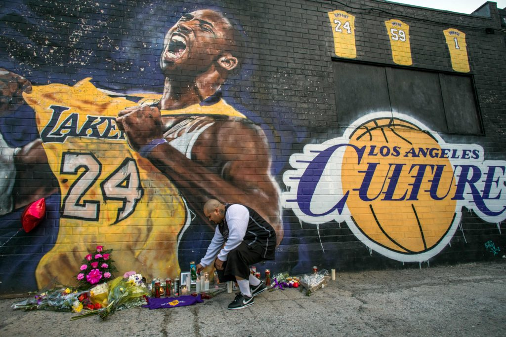 Luis Villanueva lights a candle in front of a Kobe Bryant mural by Jonas Never in downtown Los Angeles on January 26, 2020. Nine people were killed in the helicopter crash which claimed the life of NBA star Kobe Bryant and his 13-year-old daughter, Gianna Bryant. Photo by Apu Gomes/AFP/Getty Images.