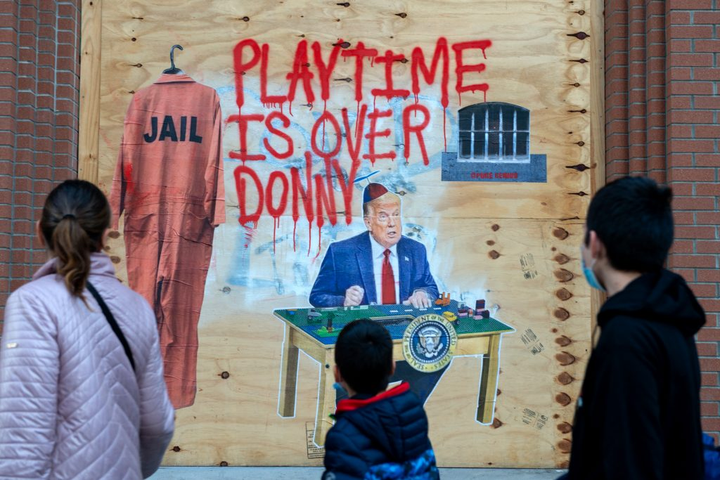 "People wearing masks walk past Donald Trump street art that reads, ""playtime is over Donny"" by Pure Genius on November 29, 2020 in New York City. Photo by Alexi Rosenfeld/Getty Images."