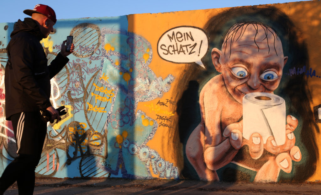 Street art in Berlin featuring the Lord of the Rings character Gollum holding a roll of toilet paper, a shopping item hoarded by consumers during the coronavirus pandemic crisis. Photo by Adam Berry/Getty Images.