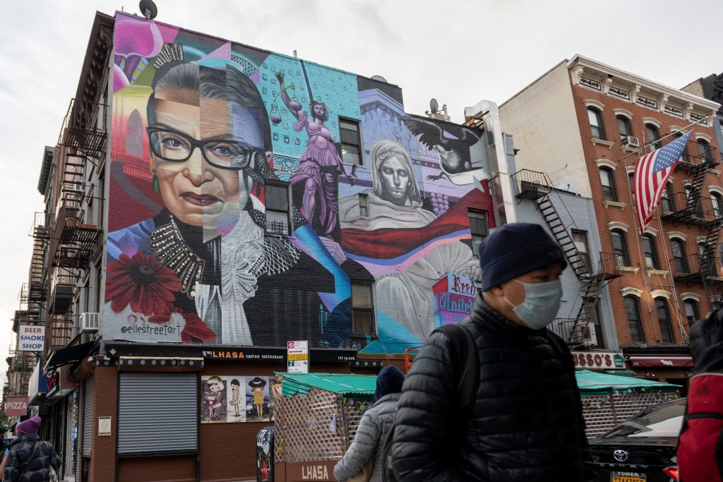 A man wearing a mask walks past a new mural by Elle Street Art of the late Supreme Court Justice Ruth Bader Ginsburg (RBG) commissioned by the Lisa Project on November 17, 2020 in New York City. Photo by Alexi Rosenfeld/Getty Images.