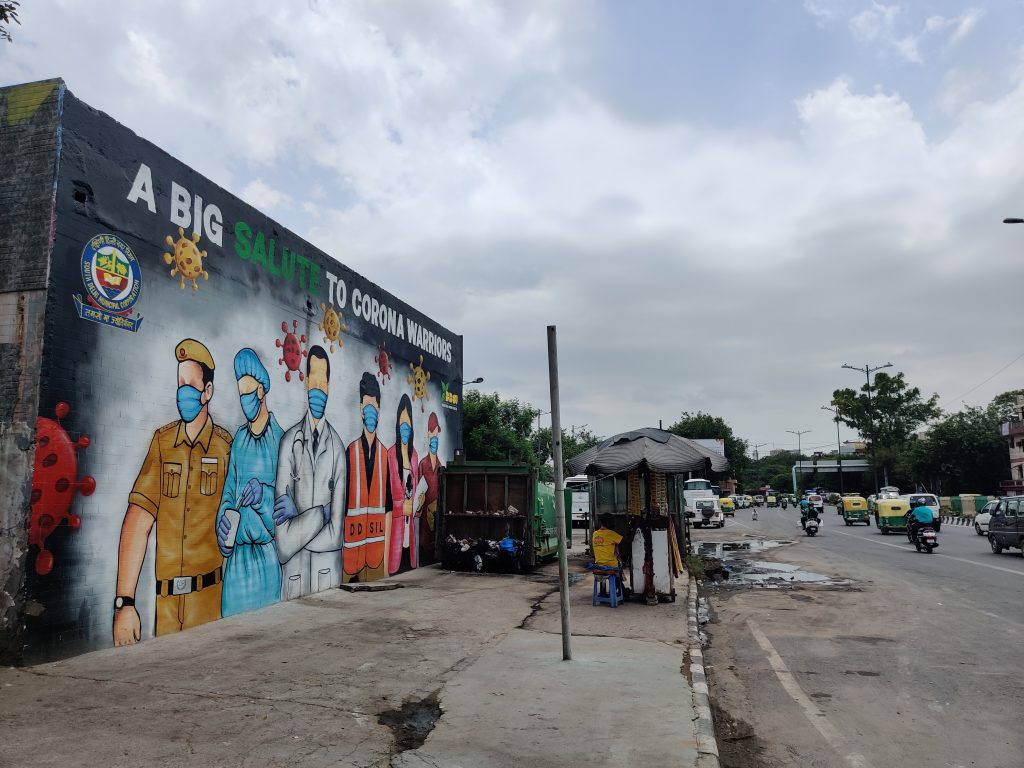 Street art adorning a public wall depicting and honoring front line corona warriors which includes, health care workers, police personnel, journalists, and sanitary workers on July 11, 2020 on the wall of municipal compactor in New Delhi, India. Photo by Pallava Bagla/Corbis via Getty Images.