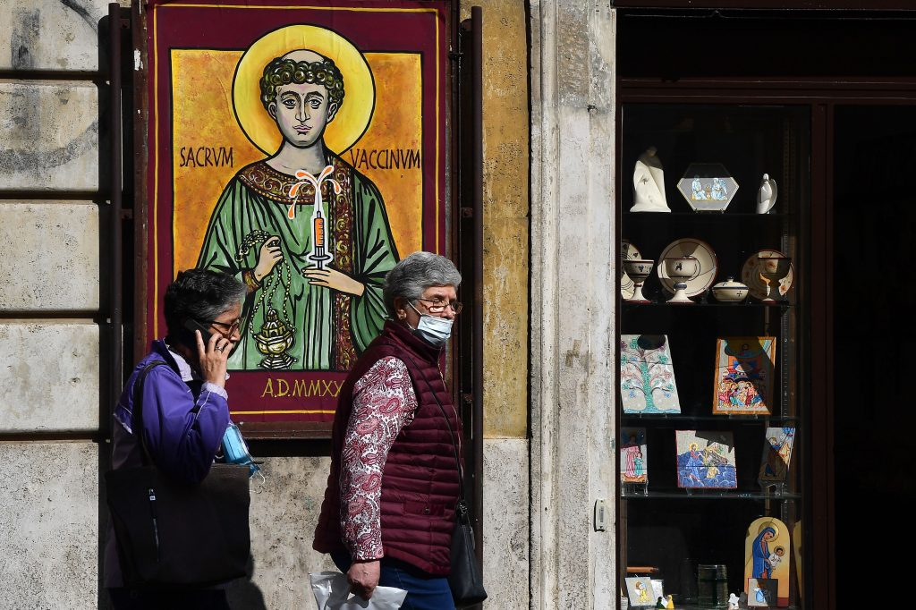 "Pedestrians walk past a poster designed and displayed overnight by Italian street artist Mauro Pallotta, aka Maupal, on October 1, 2020 in the Borgo Pio district of Rome near the Vatican, inspired by an icon of St. Stephen, representing the Saint holding a hypodermic syringe of vaccine and reading in Latin ""Sacred Vaccine"". Photo by Tiziana Fabi/AFP via Getty Images."
