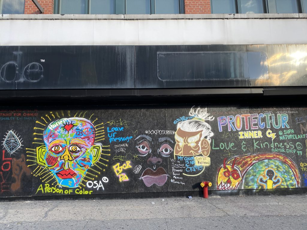 Street art on a boarded up storefront in Harlem. Photo by Sarah Cascone.