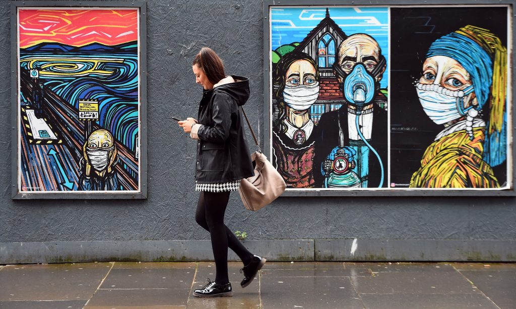 "A pedestrian walks past MandiMixUps' coronavirus street art ""Covid Collection,"" reimaginging historic artworks <em>The Scream</em>, <em>American Gothic</em>, and <em>Girl With a Pearl Earring</em> wearing masks, in Glasgow on September 2, 2020 after the Scottish government imposed fresh restrictions on the city after an rise in cases of the novel coronavirus. Photo by Andy Buchanan/AFP via Getty Images."