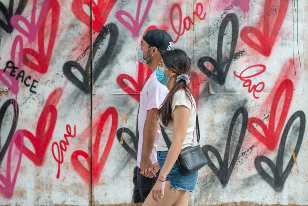 A couple wearing masks holds hands while walking past street art on August 7, 2020 in New York City. Photo by Alexi Rosenfeld/Getty Images.