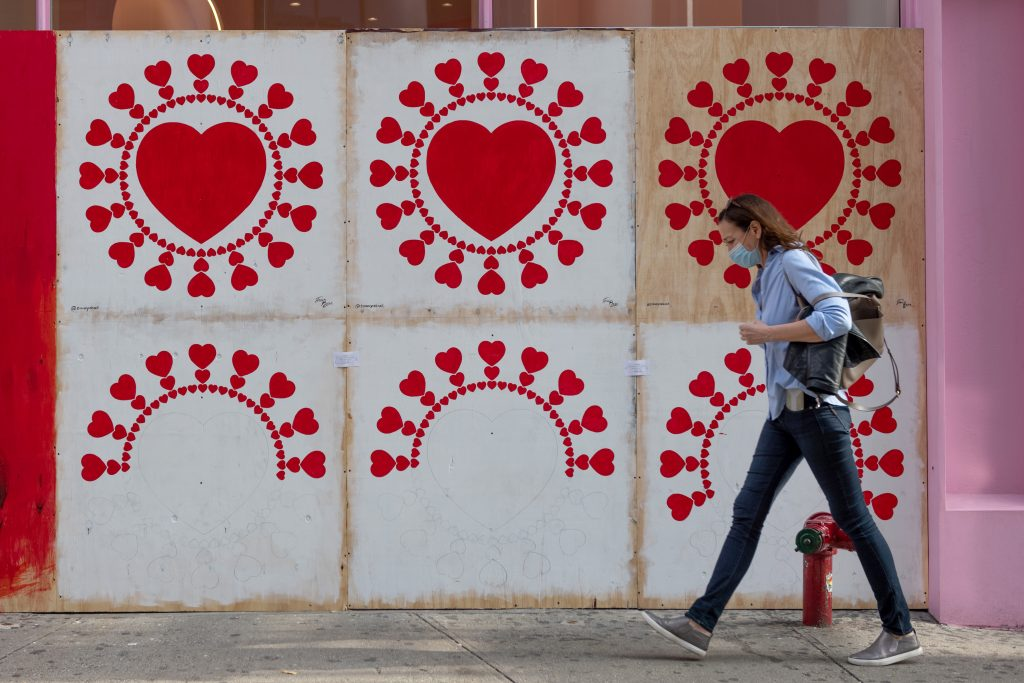 A woman wearing a mask walks past a coronavirus hearts mural by artist Timur York on the Museum of Ice Cream in SoHo on November 10, 2020 in New York City. Photo by Alexi Rosenfeld/Getty Images.