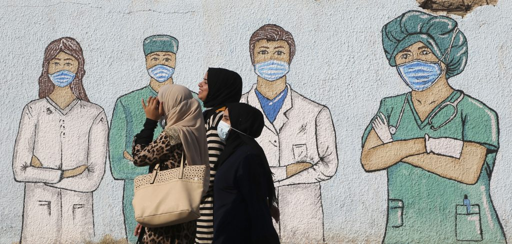 Palestinian women walk past street art showing doctors mask-clad due to the COVID-19 coronavirus pandemic, in Khan Yunis in the southern Gaza Strip, on November 12, 2020. Photo by Mohammed Abed/AFP via Getty Images.