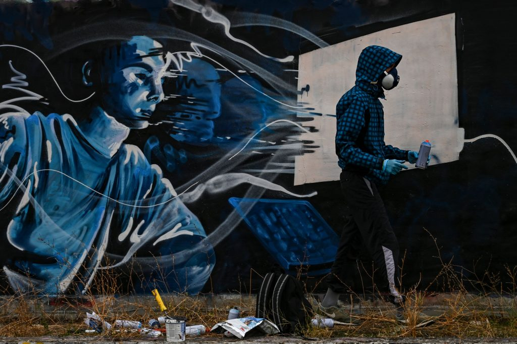 Street artist SF paints a mural on a wall in Athens, inspired by the second lockdown in Greece due to the COVID-19 pandemic, in Athens on November 25, 2020. Photo by ARIS MESSINIS/AFP via Getty Images.