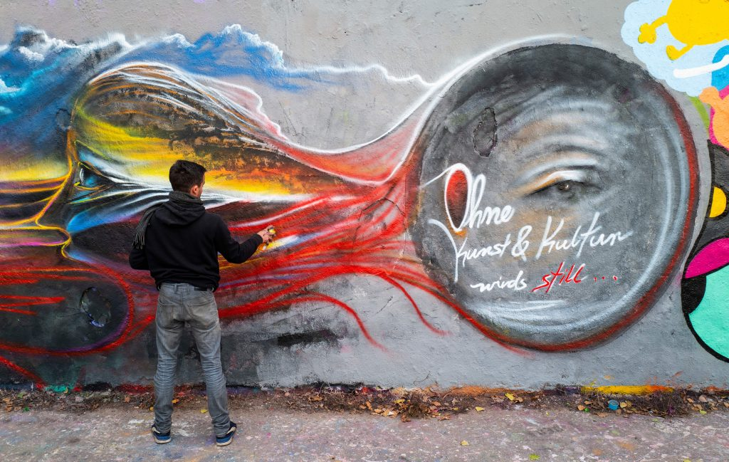 "Berlin artist S. G. Raum works on a mural featuring the words: ""Without art and culture it gets quiet..."" on a segment of the Berlin wall in Berlin's Mauerpark on November 15, 2020. Photo by John MacDougall/AFP via Getty Images."