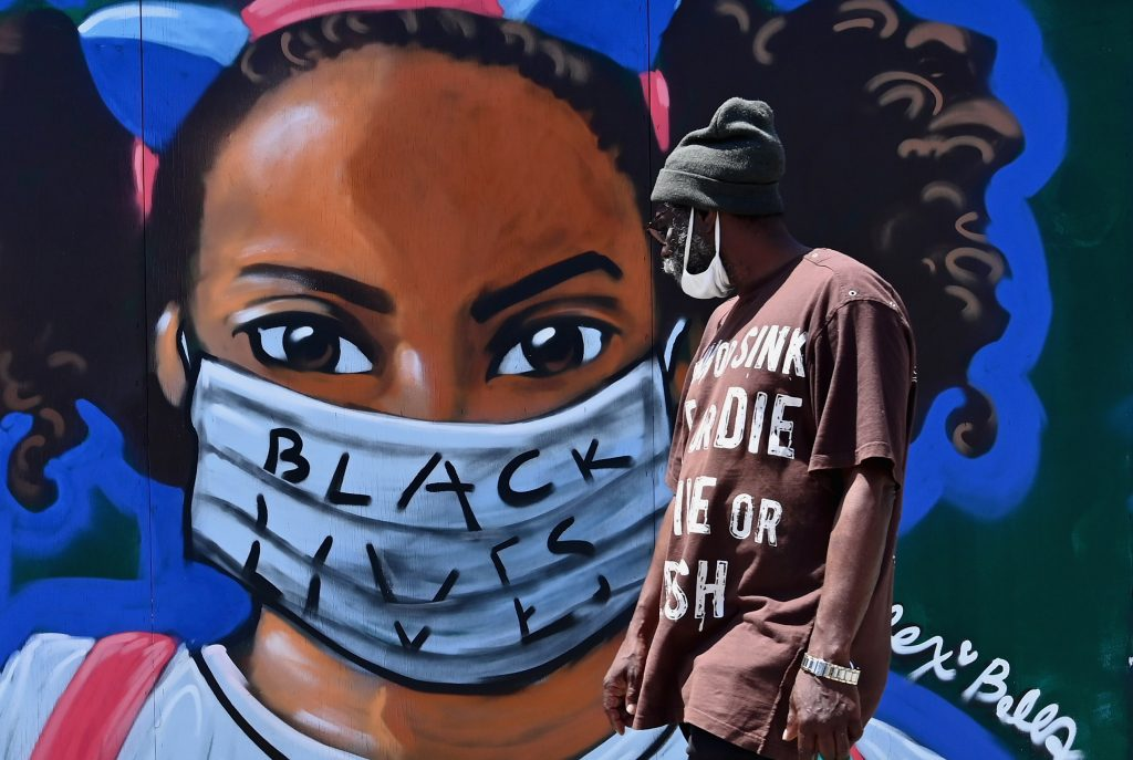 A person walks past a street mural by artist Lexi Bella on June 16, 2020 in Brooklyn. Photo by Angela Weiss/AFP via Getty Images.