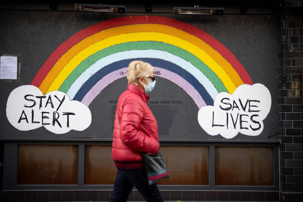 "A pedestrian wearing a face mask or covering due to the COVID-19 pandemic, walks past COVID-19 street art, advising to ""Stay Alert"" and ""Save Lives"" in central London, on November 22, 2020. Photo by Tolga Akmen/AFP via Getty Images."