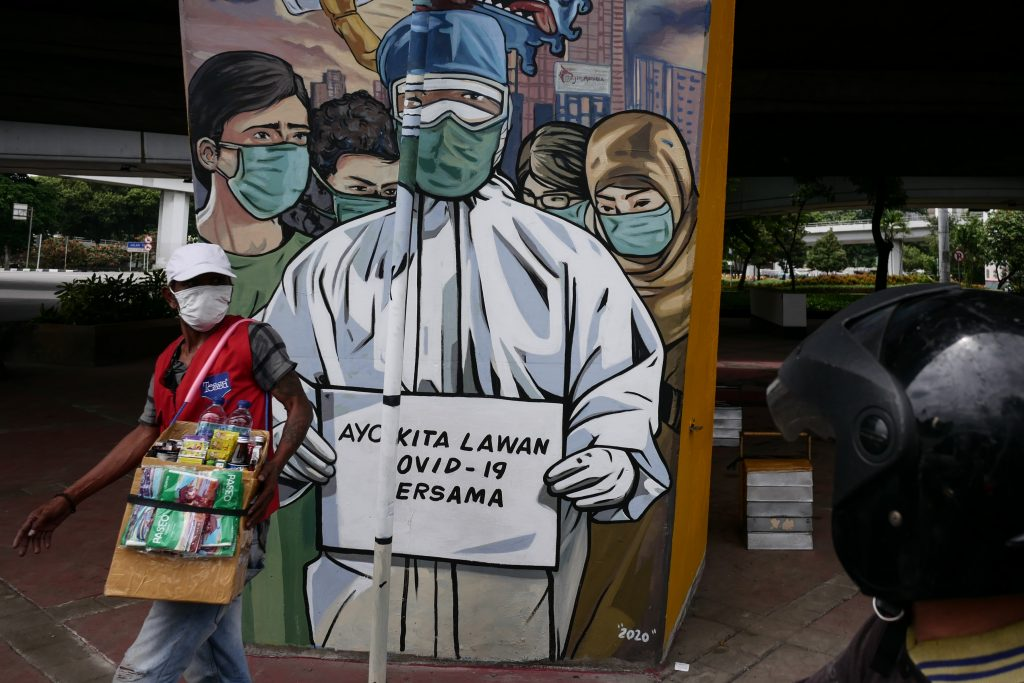A man wears a protective mask walks passes by a coronavirus (COVID-19) mural at Tomang in Jakarta, Indonesia on December 18, 2020. Photo by Anton Raharjo/Anadolu Agency via Getty Images.