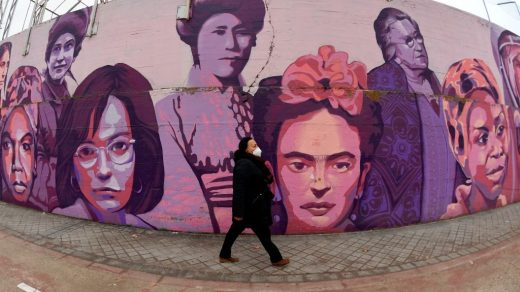 A person walks along a mural painting depicting sixteen outstanding women. Photo by Gabriel Bouys/AFP via Getty Images.