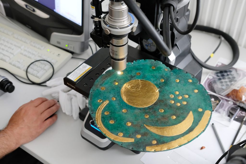 A replica of the Nebra Sky Disk being examined with a microscope in the workshop of the State Office for Monument Preservation and Archaeology Saxony-Anhalt. Photo by Sebastian Willnow/dpa-Zentralbild/dpa/picture alliance via Getty Images.
