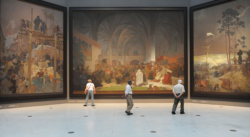 "Visitors look at paintings of the ""Slav Epic"", a cycle of 20 allegories tracing the history of the Slavic people and inspired in part by mythology, by Art Nouveau Czech artist Alfons Mucha, at the National Gallery in Prague. Michal Cizek/AFP/GettyImages."