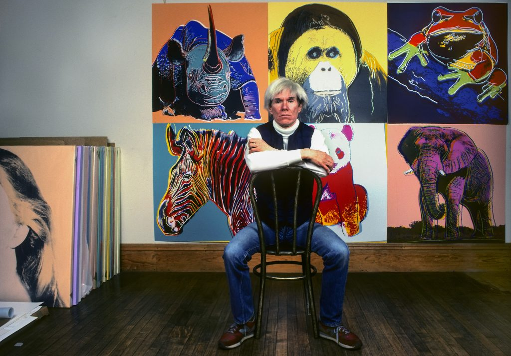 "Andy Warhol in front of several paintings in his ""Endangered Species"" series at his studio, the Factory, in Union Square, New York, New York, April 12, 1983. (Photo by Brownie Harris/Corbis via Getty Images)"
