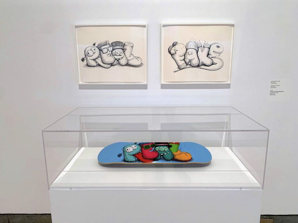 KAWS, <em>Untitled (Real)</em> and <em>Untitled (Fake)</em> and KAWS x Real Skateboards, <em>Real Skateboard</em> (2007) in case. (Photo by Ben Davis)
