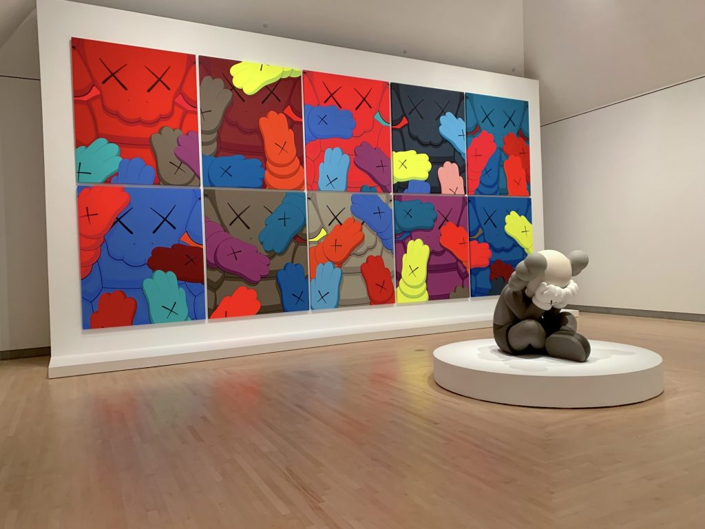 """KAWS, <em>Separated</em> (2019) with works from the """"Urge"""" series in the background. (Photo by Ben Davis)"""