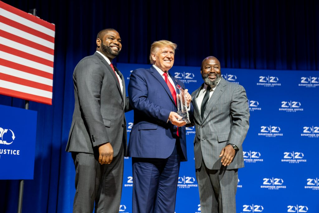 President Donald J. Trump is presented with an award by Florida State Rep. Byron Donalds, left, and Matthew Charles, one of the first inmates to benefit from the First Step Act of 2018, at the 2019 Second Step Presidential Justice Forum Friday, Oct. 25, 2019, at Benedict College in Columbia, S.C. Official White House photo by Shealah Craighead.