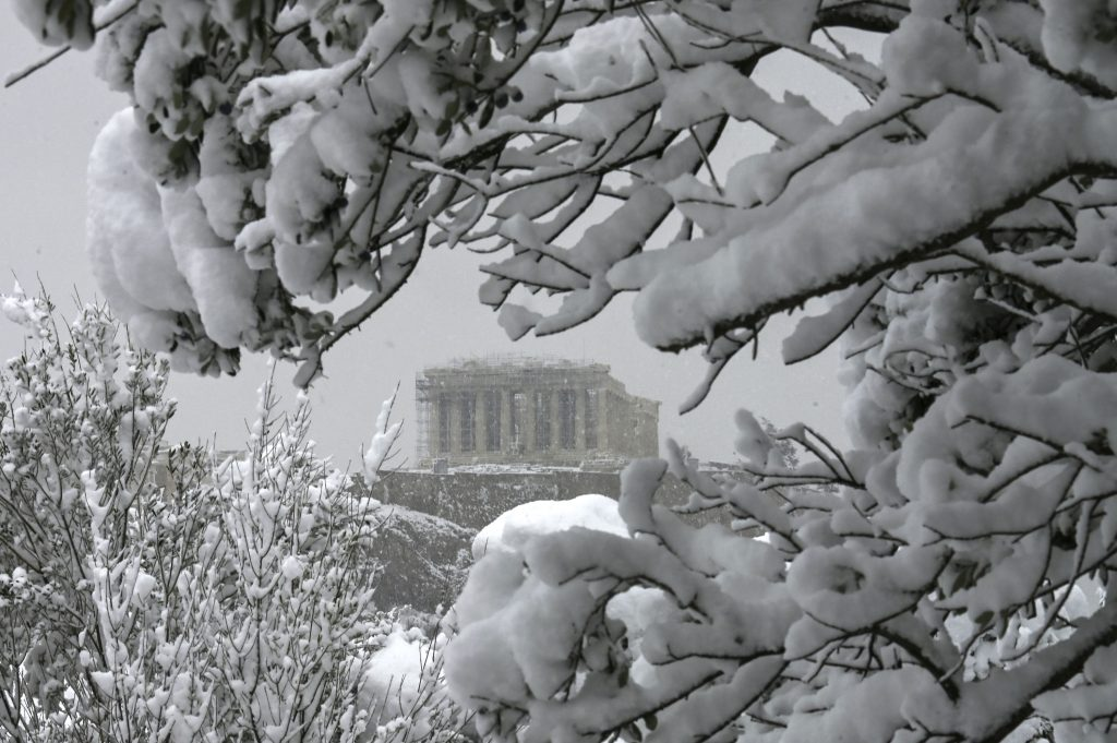 The Parthenon temple atop the Athenian Acropolis hill is pictured during heavy snowfalls in Athens on February 16, 2021. (Photo by ARIS MESSINIS/AFP via Getty Images)