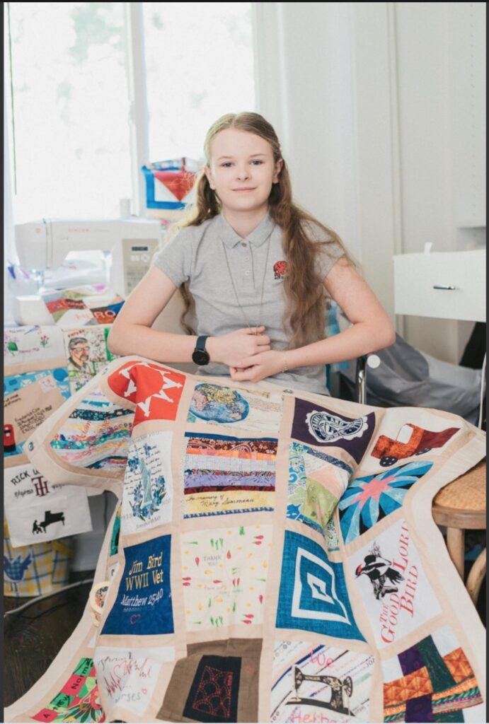 Madeleine Fugate with the COVID Memorial Quilt. Photo courtesy of the artist.