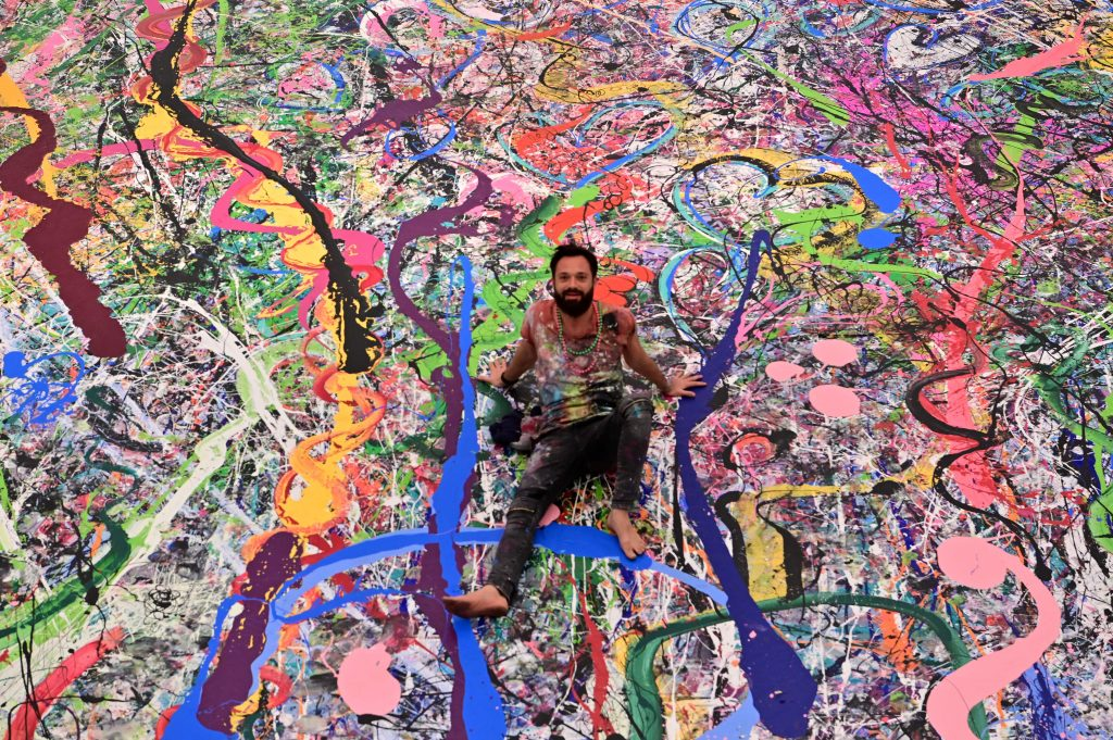 Sacha Jafri working on his record-breaking painting <em>The Journey of Humanity</em>. Photo by Giuseppe Cacace/AFP via Getty Images.