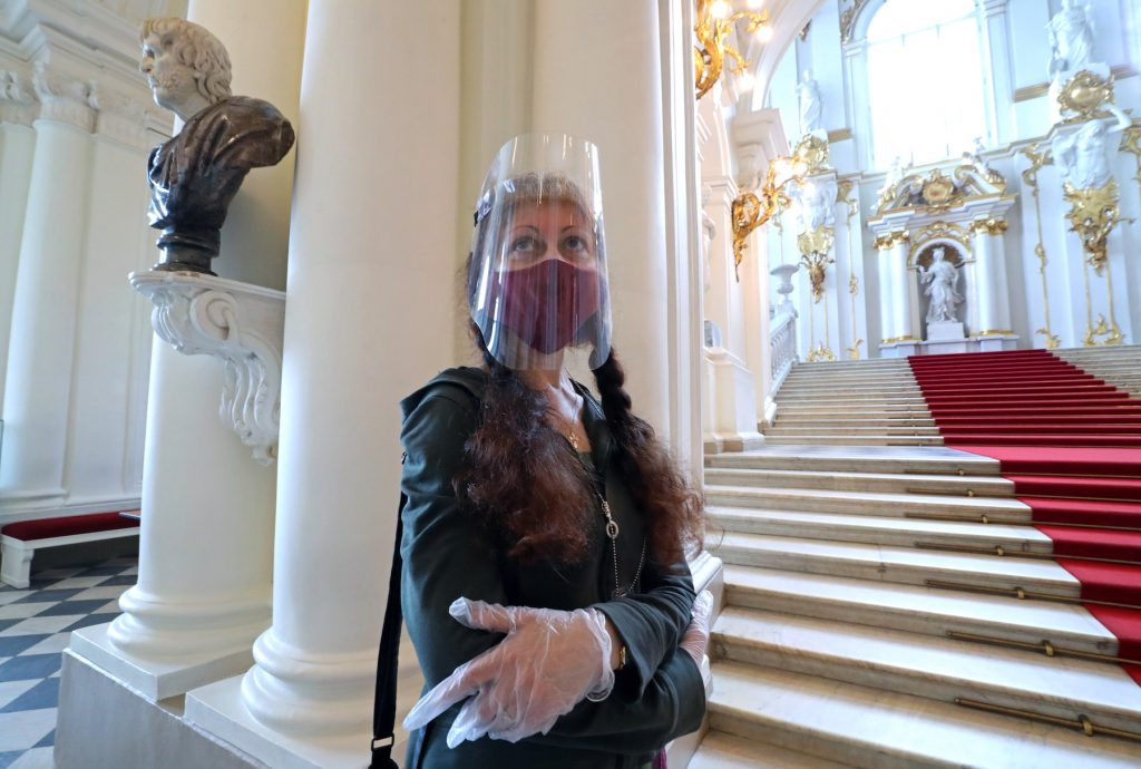 A woman with a face shield on visits the State Hermitage Museum reopening with COVID-19 lockdown restrictions lifted. Peter Kovalev/TASS (Photo by Peter KovalevTASS via Getty Images)