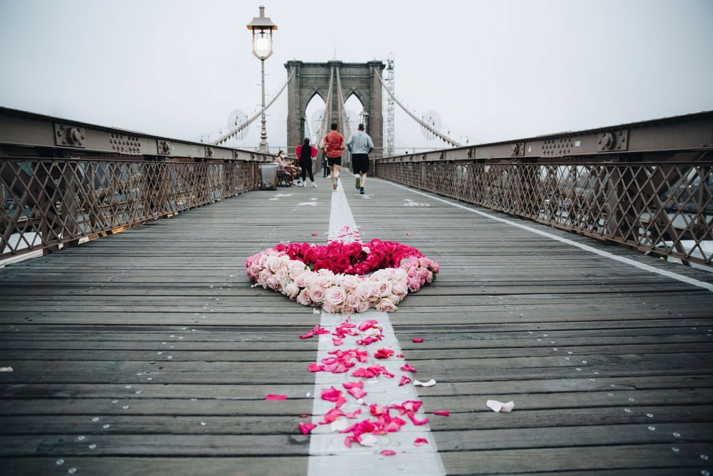 Kristina Libby, <em>The Floral Heart Project</em> on the Brooklyn Bridge. Photo by Erica Reade Images @ericareadeimages/Floral Heart Project @lightvslight.