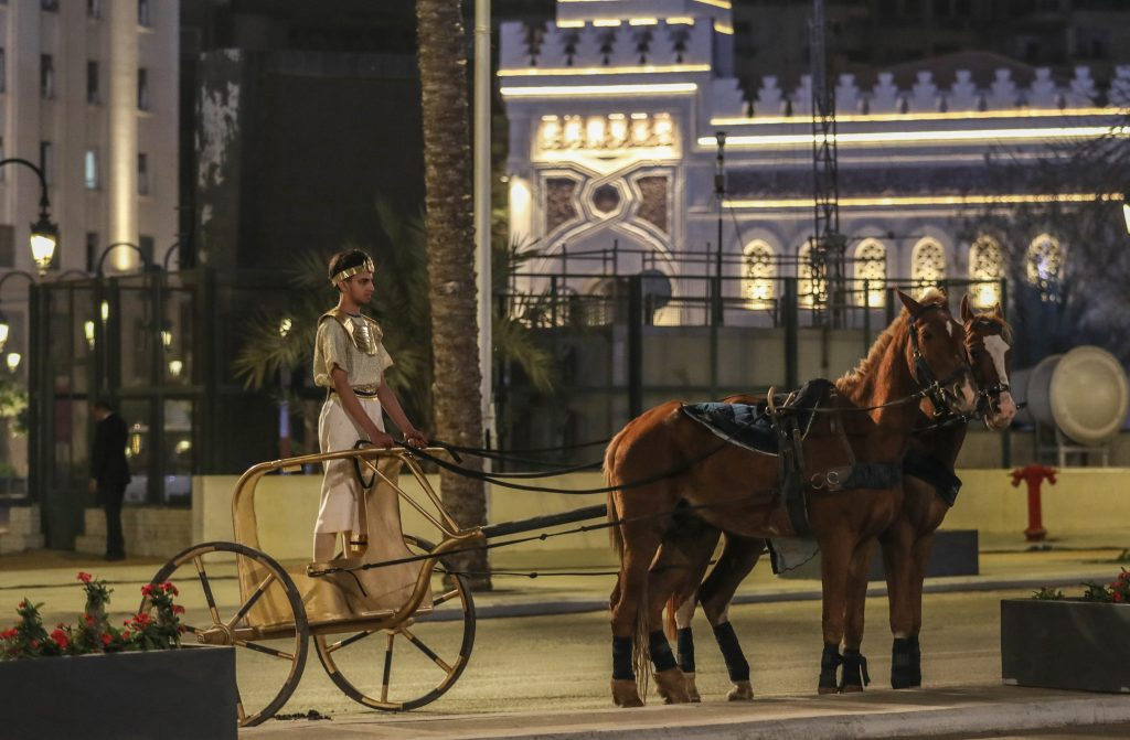 An artist in old traditional costume rides a horse-drawn carriage as specially designed vehicles transport 22 mummies in a convoy from the Egyptian Museum in Tahrir Square to the new National Museum of Egyptian Civilization, during the Pharaohs' Golden Parade in Cairo, Egypt on April 03, 2021. Photo by Stringer/Anadolu Agency via Getty Images.