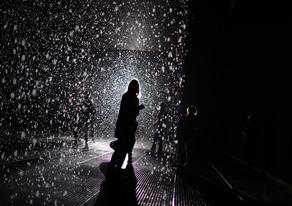"""A visitor at Random International's """"Rain Room"""" at MOMA (2012). Photo: TIMOTHY CLARY/AFP via Getty Images."""