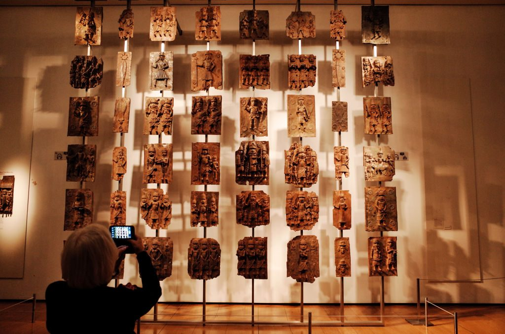 A visitor takes photos of the contentious Benin bronzes that are on display at the British Museum in London. Photo: David Cliff/SOPA Images/LightRocket via Getty Images.