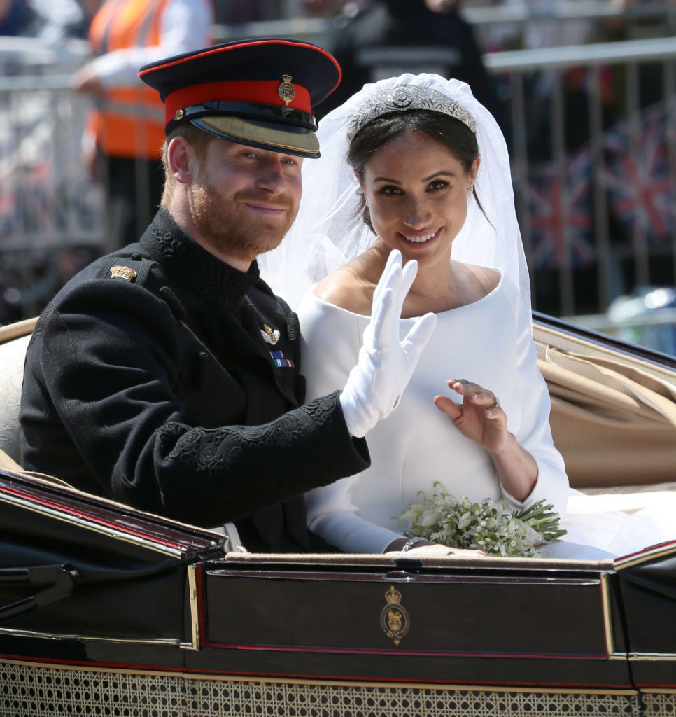 Prince Harry, Duke of Sussex and Meghan, Duchess of Sussex wave from the Ascot Landau Carriage during their carriage procession on Castle Hill outside Windsor Castle in Windsor, on May 19, 2018 after their wedding ceremony. Photo by Aaron Chown/WPA Pool/Getty Images.