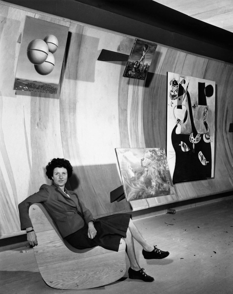 Art collector Peggy Guggenheim poses with paintings at the Museum of Modern Art in New York City, Oct. 22, 1942. (AP Photo)