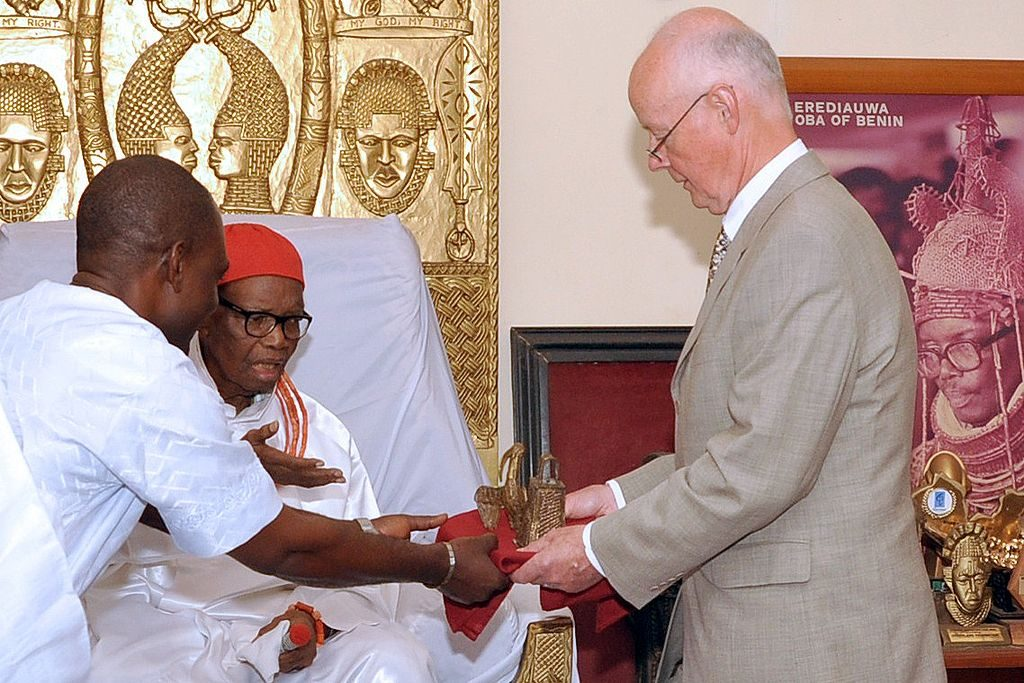 Retired hospital consultant Mark Walker (R) hands over two bronze artefacts he returned to the Benin kingdom to the Oba (King) of Benin, Uku Akpolokpolo Erediauwa I, during a ceremony in Benin City, Nigeria, on June 20, 2014. Photo: Kelvin Ikpea/AFP via Getty Images.