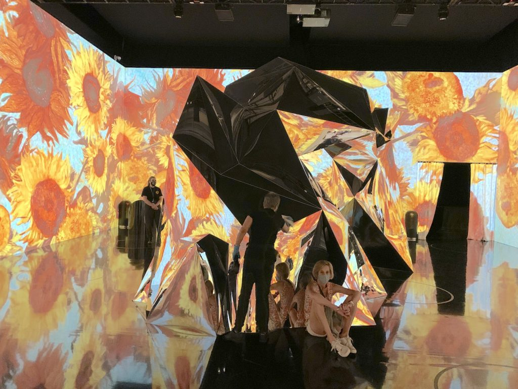 """A worker polishes one of the large mirrored sculptures in """"Immersive Van Gogh."""" Photo by Ben Davis."""