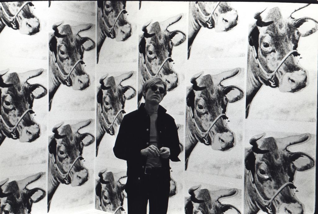 Andy Warhol with his Cow wallpaper at Leo Castelli (1966). Photo by Fred W. McDarrah, courtesy of Steven Kasher Gallery.