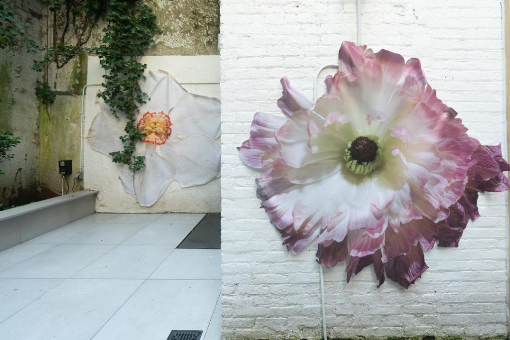 """Benjamin Langford's flowers are installed on the walls of the gallery's courtyard in """"但聞人語響:Yet, Only Voice Echoed"""" at Fu Qiumeng Fine Art. Photo courtesy of Fu Qiumeng Fine Art."""