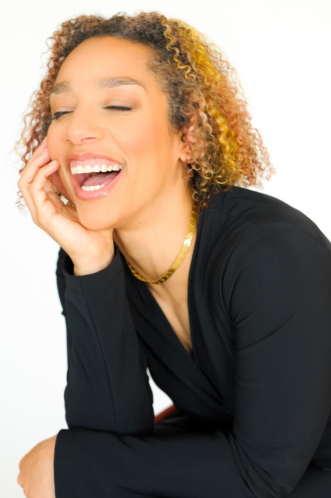 Alice Sheppard. Image description: A Black woman leans forward and smiles brightly, teeth showing and eyes closed, as she rests her chin in her palm. She has light brown skin, curly shoulder-length hair with subtle highlights, and wears a black blouse and sleek gold necklace.